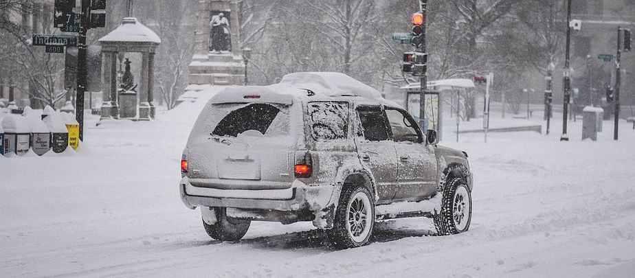 SUV driving down snowy Road